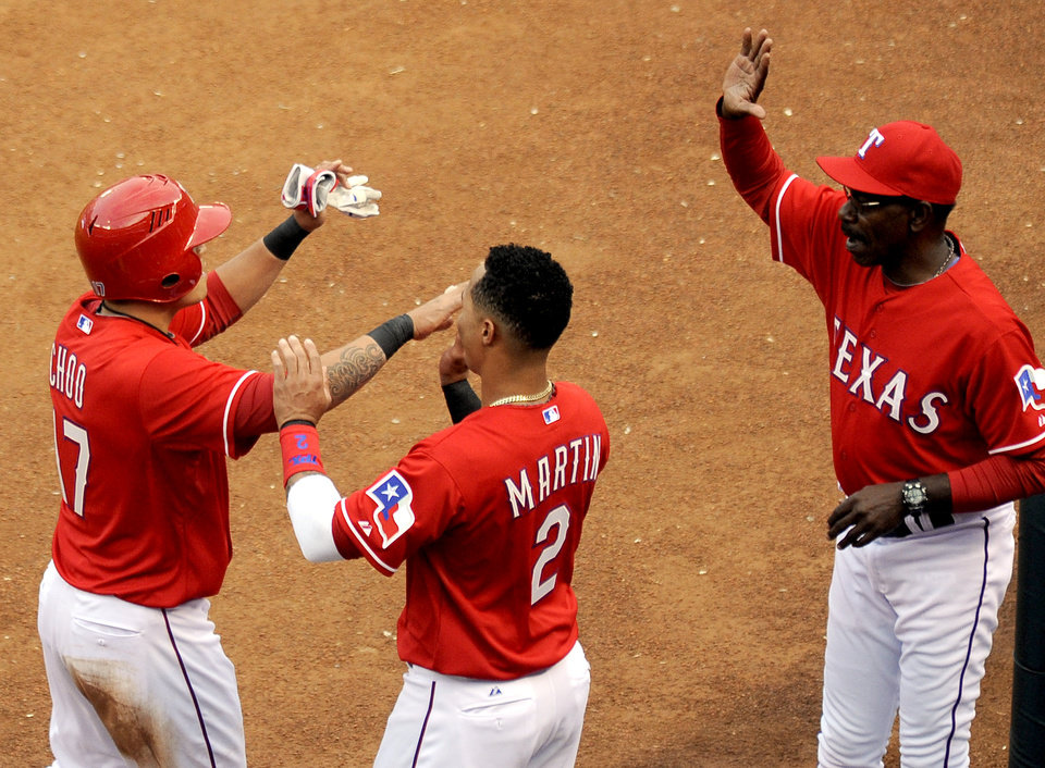 Photo - Texas Rangers' Shin-Soo Choo, left, is congratulated by Leonys Martin (2) and manager Ron Washington after scoring a run in the first inning of a baseball game against the Chicago White Sox, Saturday, April 19, 2014, in Arlington, Texas. (AP Photo/Matt Strasen)