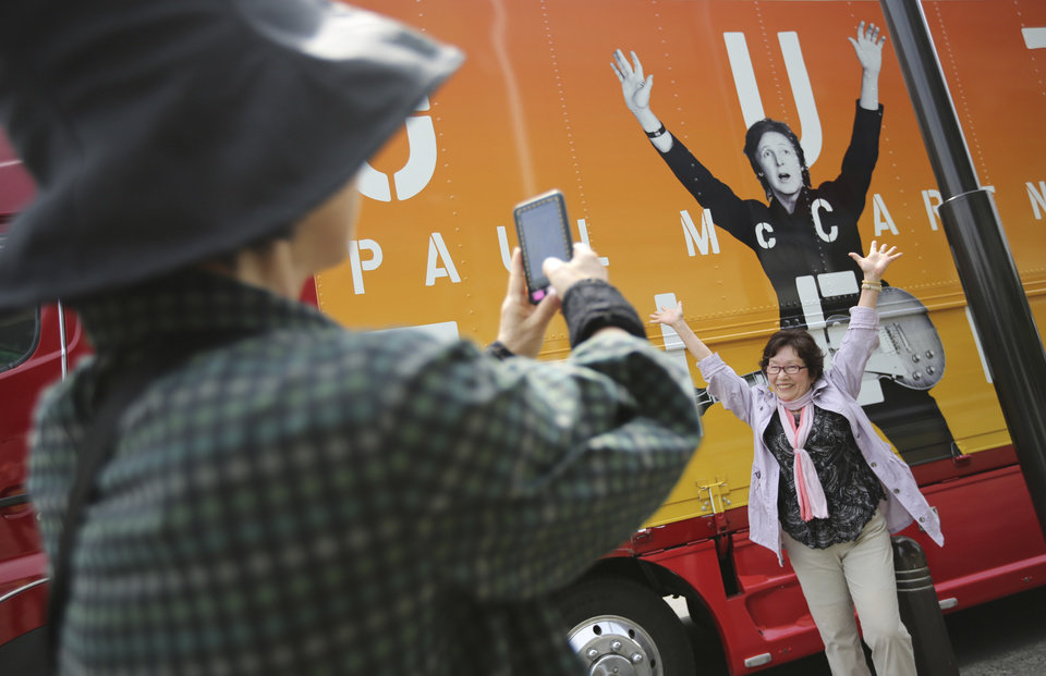 Photo - Fans take photos in front of a promotional truck bearing an image of Paul McCartney at Nippon Budokan hall in Tokyo, Tuesday, May 20, 2014. Paul McCartney is canceling his entire Japan tour because of illness including the one set for Wednesday at Nippon Budokan hall, where The Beatles performed during their first Japan tour in 1966. (AP Photo/Eugene Hoshiko)