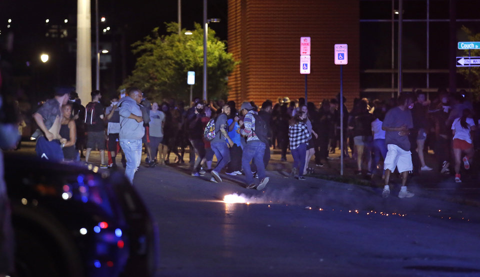 Photo - Protestors run from a non-lethal weapon  in front of the Oklahoma City Police Department in Oklahoma City, Sunday, May 31, 2020. The protest was in response to the death of George Floyd. [Sarah Phipps/The Oklahoman]