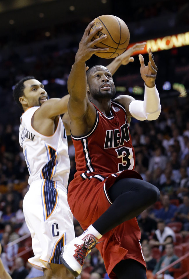 Miami Heat guard Dwyane Wade (3) goes up for a shot against Charlotte Bobcats guard Gerald Henderson during the first half of an NBA basketball game, Monday, Feb. 4, 2013 in Miami. (AP Photo/Wilfredo Lee)