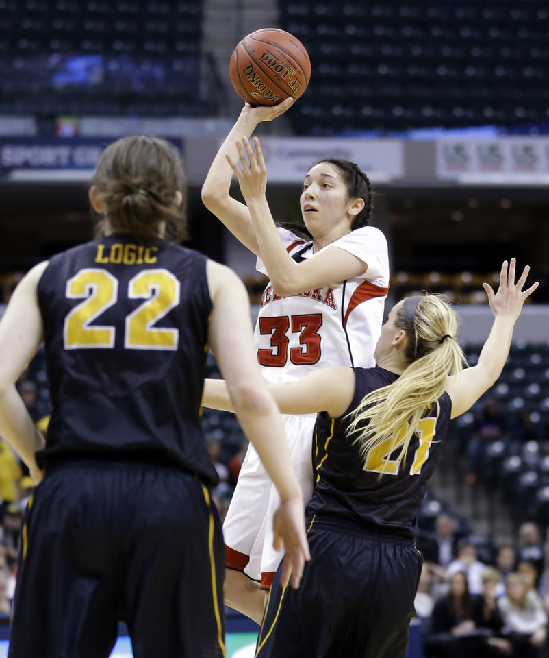 Photo - Nebraska guard Rachel Theriot (33) shoots over Iowa guards Samantha Logic, left, and Sadie Murren in the second half of an NCAA college basketball game in the finals of the Big Ten women's tournament in Indianapolis, Sunday, March 9, 2014. Nebraska defeated Iowa 72-65. (AP Photo/Michael Conroy)