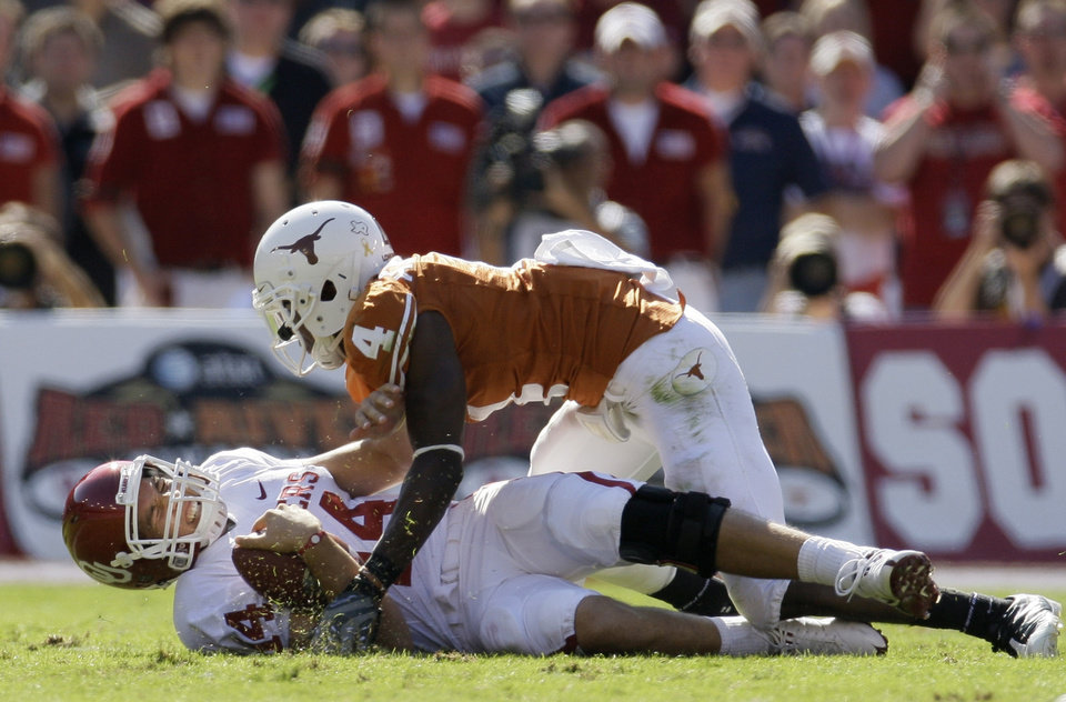 Photo - Oklahoma quarterback Sam Bradford, bottom, grimaces to being sacked by Texas cornerback Aaron Williams in the first half of an NCAA football game, Saturday, Oct. 17, 2009, in Dallas. Bradford did not return to the game following an injury on the play. (AP Photo/Tony Gutierrez)