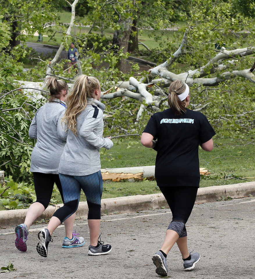 Photo - Runners pass fallen trees at NW 28 and Harvey Parkway from the previous day's thunderstorms during the Oklahoma City Memorial Marathon in Oklahoma City, Sunday, April 30, 2017. Photo by Nate Billings, The Oklahoman