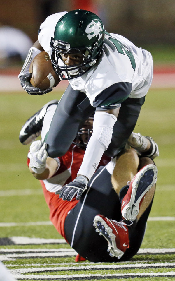 Edmond Santa Fe's Cameron Westbrook (20) is stopped by Yukon's Brandon Andraszek (10) during a high school football game between Yukon and Edmond Santa Fe in Yukon, Okla., Friday, Sept. 7, 2012. Photo by Nate Billings, The Oklahoman