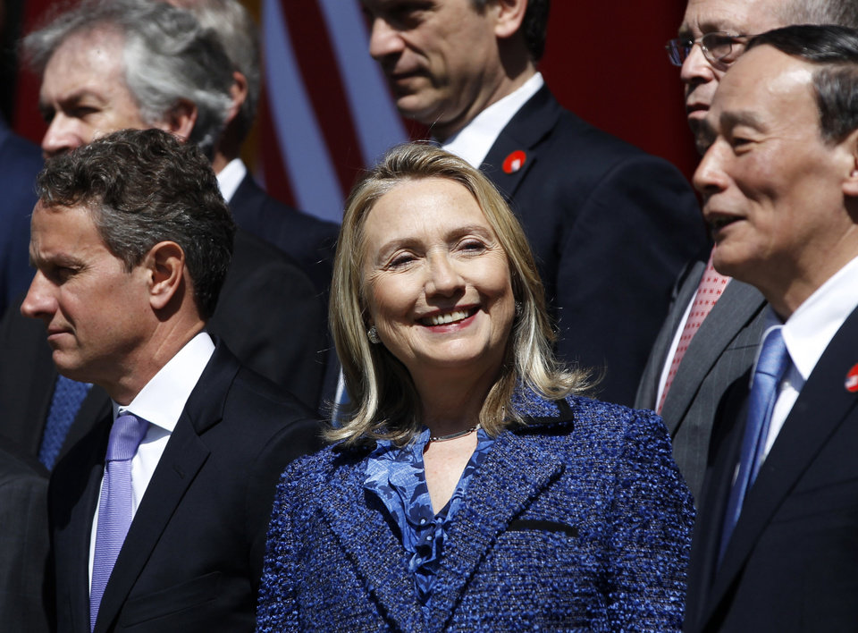 Photo -   U.S. Secretary of State Hillary Rodham Clinton, center, smiles next to U.S. Treasury Secretary Timothy Geithner, left, and Chinese Vice Premier Wang Qishan, right, during a photo session after the opening ceremony of the U.S.-China Strategic and Economic Dialogue at the Diaoyutai state guesthouse in Beijing Thursday, May 3, 2012. (AP Photo/Shannon Stapleton, Pool)