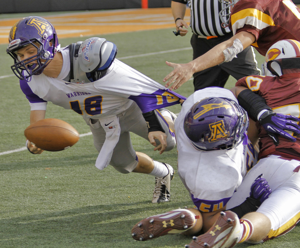 Anadarko's Brandon Pollard (18) is brought down as he throws the ball during the Class 4A Oklahoma state championship football game between Anadarko and Clinton at Boone Pickens Stadium on Saturday, Dec. 1, 2012, in Stillwater, Okla.   Photo by Chris Landsberger, The Oklahoman
