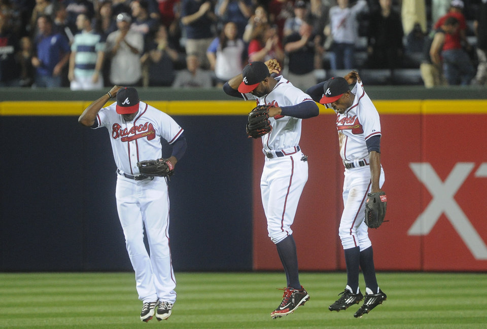 Atlanta Braves left fielder Justin Upton, left, right fielder Jason Heyward, and center fielder B.J. Upton, right, lift themselves up in celebration after beating the Kansas City Royals in a baseball game, Tuesday, April 16, 2013, in Atlanta. Atlanta won 6-3. (AP Photo/John Amis)