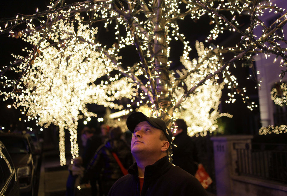 "Photo - This Dec. 4, 2012 photo shows Erik Hall of Rochester, N.Y., looking up at the elaborate holiday displays during a tour in the Brooklyn borough of New York. Each holiday season, tour operator Muia takes tourists from around the world on his ""Christmas Lights & Cannoli Tour"" visiting the Brooklyn neighborhoods of Dyker Heights and Bay Ridge, where locals take pride in over-the-top holiday light displays.  (AP Photo/Seth Wenig)"