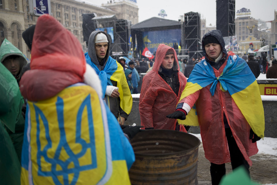 Photo - Pro-European Union activists wearing Ukrainian National flags warm themselves near a bonfire on the Independence Square in KIev, Ukraine, Monday, Dec. 9, 2013. The protesters rose up against President Viktor Yanukovych after he spiked a deal for integration with the European Union and decided to restore trade ties with Russia instead. (AP Photo/Alexander Zemlianichenko)