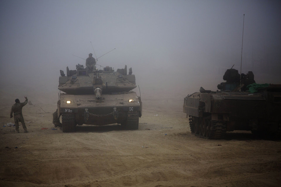 Photo - An Israeli tank moves through the morning mist near the Israel and Gaza border Thursday, July 24, 2014. Israeli tanks and warplanes bombarded the Gaza Strip on Thursday, as Hamas militants stuck to their demand for the lifting of an Israeli and Egyptian blockade in the face of U.S. efforts to reach a cease-fire. (AP Photo/Dusan Vranic)