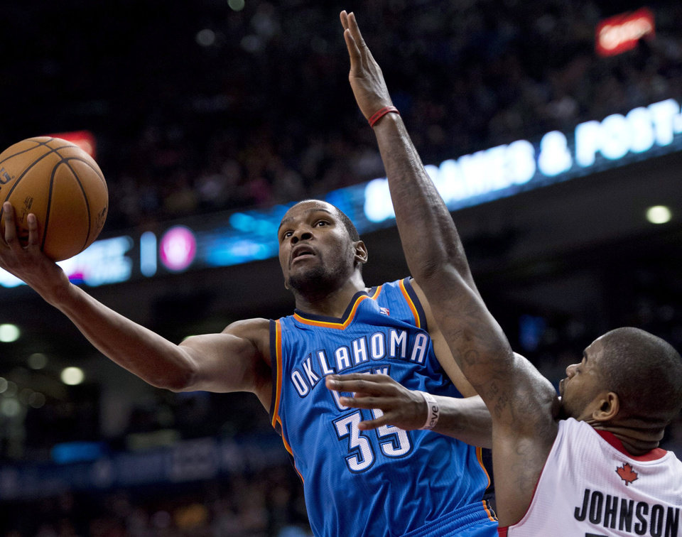 Photo - Oklahoma City Thunder forward Kevin Durant (35) drives to the basket past Toronto Raptors forward Amir Johnson (15) during the second half of an NBA basketball game in Toronto on Sunday, Jan. 6, 2013. (AP Photo/The Canadian Press, Frank Gunn) ORG XMIT: FNG110