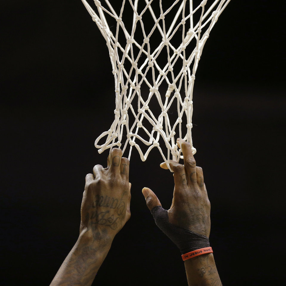 Photo - Milwaukee Bucks' Larry Sanders grabs the net during a break in the action in the first half of an NBA basketball game against the Phoenix Suns on Wednesday, Jan. 29, 2014, in Milwaukee. (AP Photo/Jeffrey Phelps)