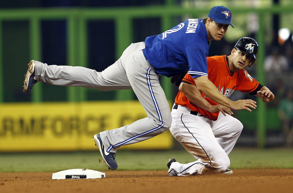 Photo -   After Miami Marlins runner Justin Ruggiano, right, was forced out at second both he and Toronto Blue Jays second baseman Kelly Johnson, front, watch to see if Omar Infante was safe at first during the fourth inning of a baseball game in Miami, Saturday, June 23, 2012. Infante was safe at first. (AP Photo/J Pat Carter)