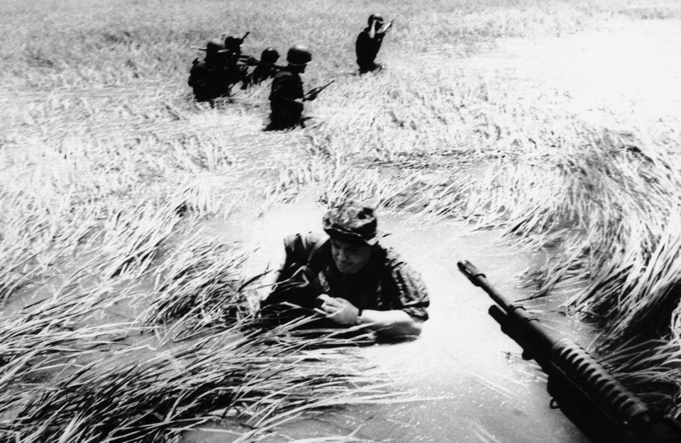 Photo -   FILE - In this May 11, 1965 file photo, Associated Press photographer Horst Faas tries to get back on a U.S. helicopter after a day out with Vietnamese rangers in a flooded plain of reeds. Faas, a prize-winning combat photographer who carved out new standards for covering war with a camera and became one of the world's legendary photojournalists in nearly half a century with The Associated Press, Thursday May 10, 2012. He was 79. (AP Photo/File)
