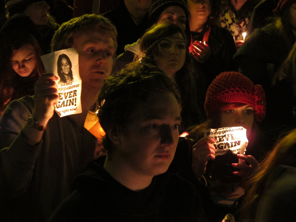 Photo -   Abortion rights protesters hold candles and pictures in a vigil for Savita Halappanavar outside Ireland's government headquarters in Dublin Saturday, Nov. 17, 2012. Thousands marched to the spot to demand that the government draft a law defining when abortions can be performed to save a woman's life. Ireland has been shocked by the death of Halappanavar, a 31-year-old Indian dentist who died of blood poisoning after being denied an abortion in a Dublin hospital last month. (AP Photo/Shawn Pogatchnik)