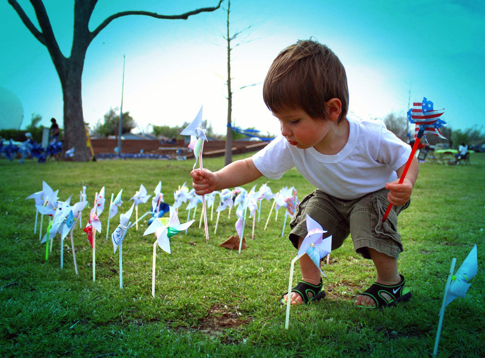 Izaak Burger, 19 months, plants a pinwheel in the grass during the �A Children�s Garden: Raising  Awareness for Child Abuse Prevention� event  Saturday at Andrews Park in Norman.  PHOTO BY LYNETTE LOBBAN, FOR THE OKLAHOMAN