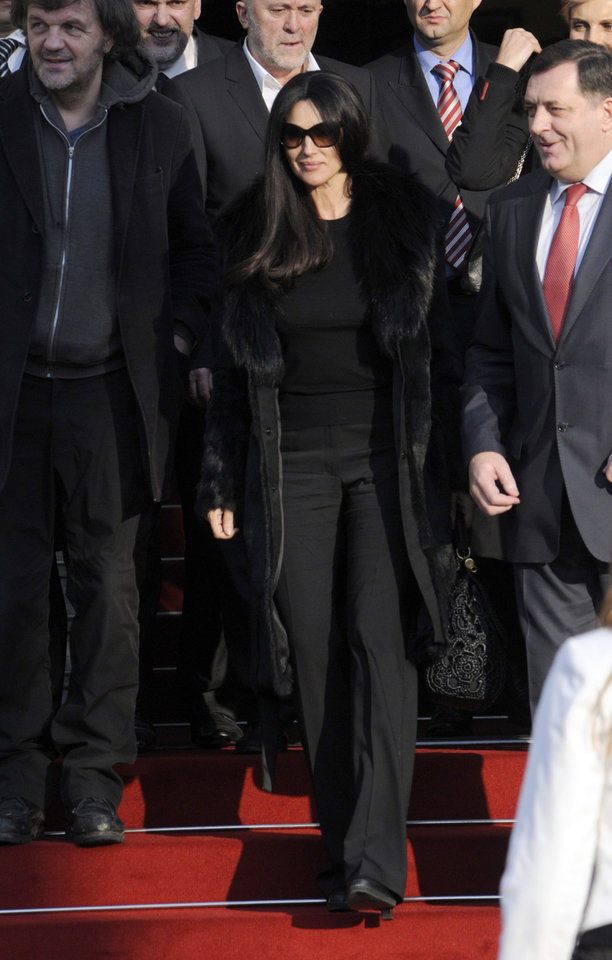 Italian actress Monica Bellucci accompanied with Milorad Dodik, right, president of the Republic of Srpska, right, and Emir Kusturica film director, left, during a visit to Bosnian town of Banja Luka, 240 kms northwest of Sarajevo, Bosnia, on Saturday, Jan. 19, 2013. (AP Photo/Radivoje Pavicic )