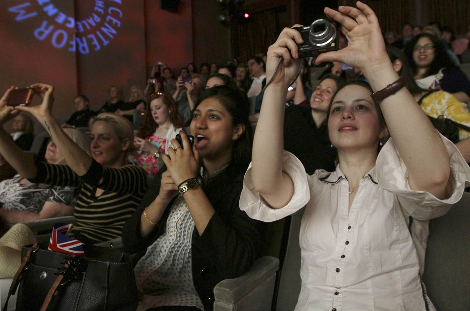 Photo - Cristina Gall, right, takes a picture of the screen as she and others watch coverage of the wedding of Prince William and Kate Middleton as it is broadcast live from London during the Paley Center's royal wedding viewing party Friday April 29, 2011 in New York. (AP Photo/Tina Fineberg) ORG XMIT: NYTF105