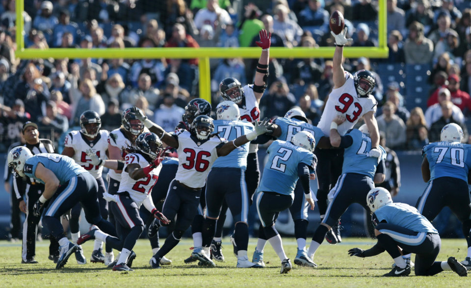 Photo - Tennessee Titans kicker Rob Bironas (2) boots a 42-yard field goal as Houston Texans defenders D.J. Swearinger (36) and Jared Crick (93) try to block the ball in the second quarter of an NFL football game on Sunday, Dec. 29, 2013, in Nashville, Tenn. (AP Photo/Wade Payne)