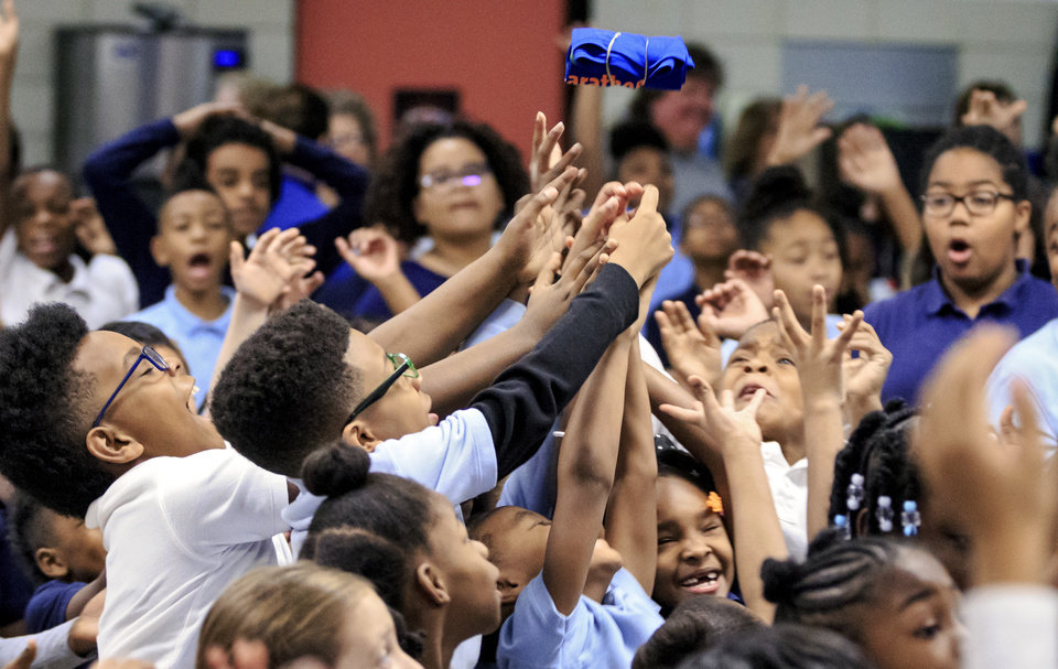 Photo -  Students at Stanley Hupfeld Academy reach for prizes Friday during the Kids Marathon rally to kick off the