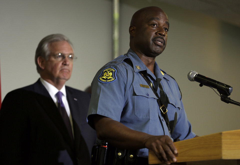 Photo - Capt. Ron Johnson of the Missouri Highway Patrol speaks during a news conference as Missouri Gov. Jay Nixon, left, listens during news conference Thursday, Aug. 14, 2014, in St. Louis. Nixon has announced the Missouri State Highway Patrol, led by Capt. Johnson, will take over the supervision of security in the St. Louis suburb that's been the scene of violent protests since a police officer fatally shot an unarmed black teenager, the governor announced Wednesday.(AP Photo/Jeff Roberson)