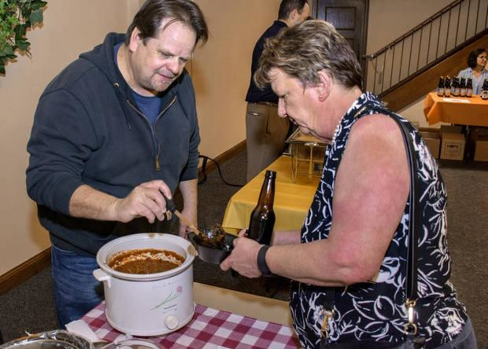 Photo -  Gayle Hough, of Oklahoma City, tests out the chili made by Mark Lambert. [PHOTO BY ERIECH TAPIA, FOR THE OKLAHOMAN]