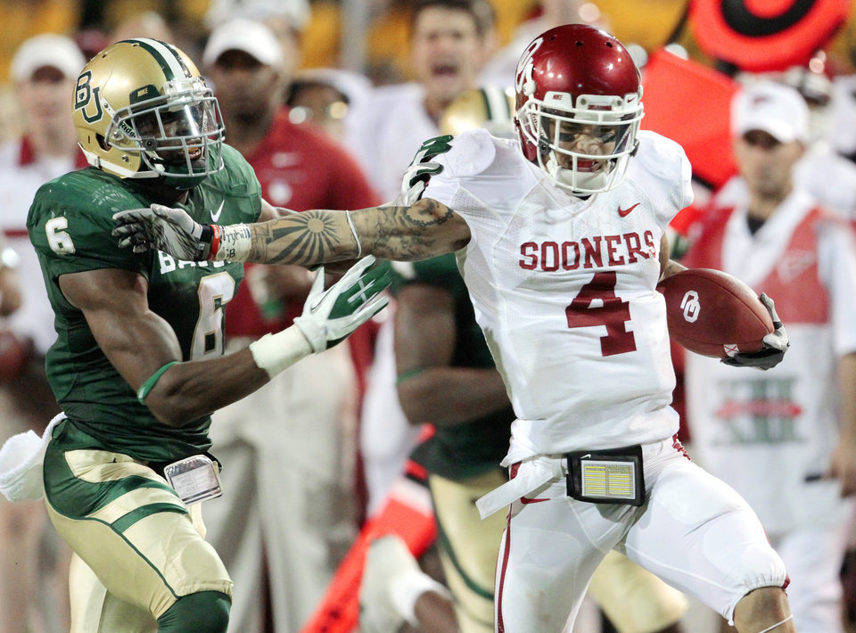 Oklahoma\'s Kenny Stills (4) catches long pass and is run out of bounds by Baylor\'s Ahmad Dixon (6) during a November 2011 game in Waco, Texas. Stills is the favorite to take over as OU\'s punt returner. Photo by Steve Sisney, The Oklahoman