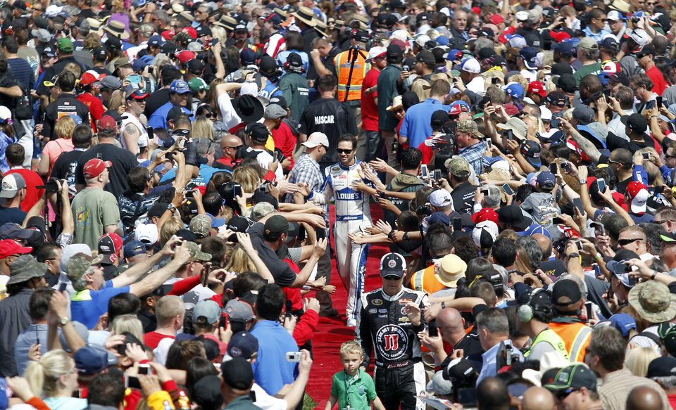 Photo - Jimmie Johnson, center, and Kevin Harvick, below, walk through the crowd during introductions for the NASCAR Sprint Series auto race in Fontana, Calif., Sunday, March 23, 2014. Kyle Busch won the race. (AP Photo/Alex Gallardo)