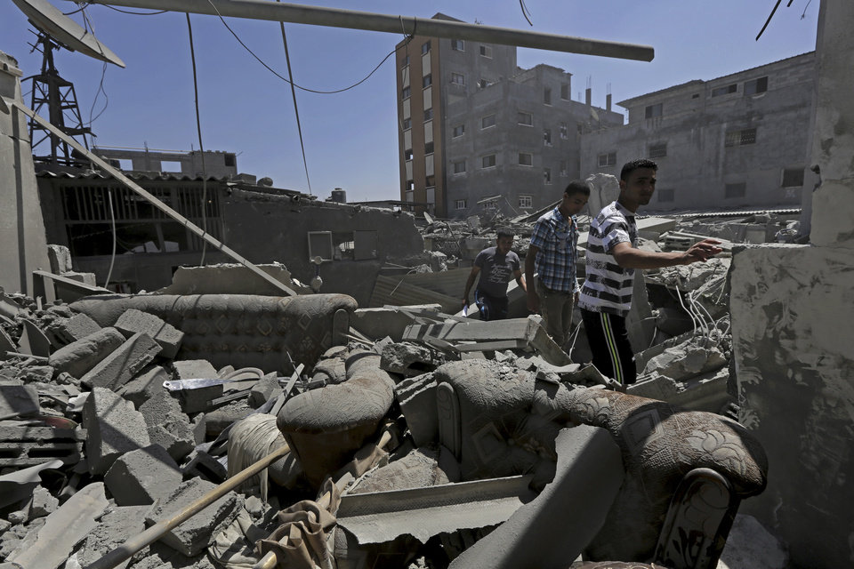 Photo - Palestinians inspect the rubble of a house belonging to the Abu Hamada family after an Israeli strike in Jebaliya refugee camp, in the northern Gaza Strip, Monday, Aug. 25, 2014. Several people were wounded in an airstrike on houses in Jebaliya refugee camp, according to Gaza health official Ashraf al-Kidra. (AP Photo/Adel Hana)