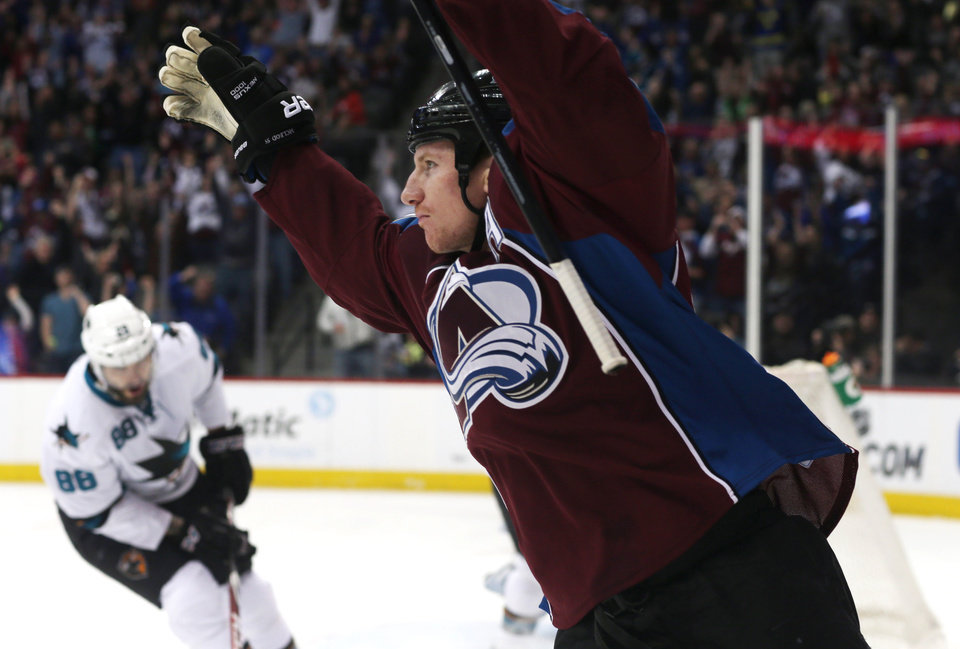 Photo - Colorado Avalanche left wing Cody McLeod, front, celebrates his short-handed goal as San Jose Sharks right wing Brent Burns reacts in the background in the first period of an NHL hockey game on Saturday, March 29, 2014, in Denver. (AP Photo/David Zalubowski)