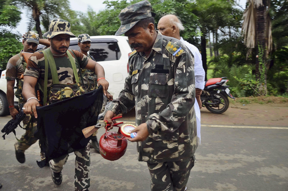 A bomb squad member defuses a suspected timer fitted device at Bodhgaya, about 130 kilometers (80 miles) south of Patna, the capital of the eastern Indian state of Bihar, Sunday, July 7, 2013. A series of blasts hit three Buddhist sites in eastern India early Sunday, injuring at least two people and drawing condemnation from Prime Minister Manmohan Singh. (AP Photo/Manish Bhandari)