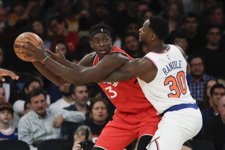 Photo -  Toronto Raptors' Pascal Siakam (43) protects the ball from New York Knicks' Julius Randle (30) during Friday night's game in NewYork. [AP Photo/Frank Franklin II]