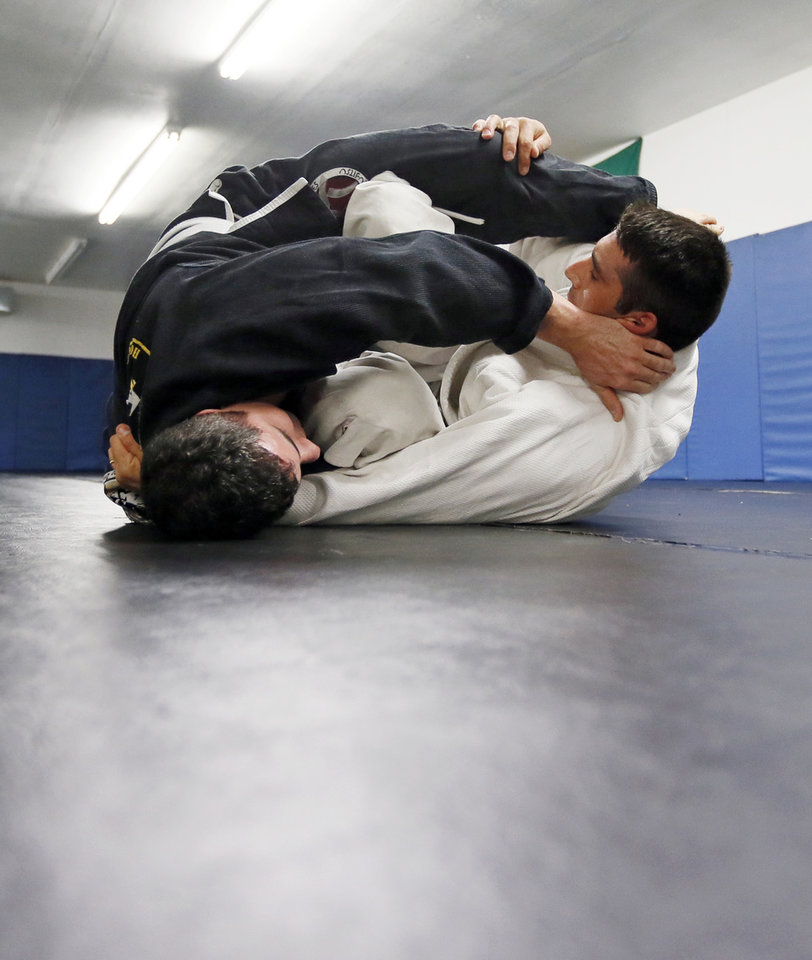 Photo -  Troopers Brad Giulioli, left, and Brian Costanza practice jujitsu in Okmulgee. [Photo by Nate Billings, The Oklahoman]