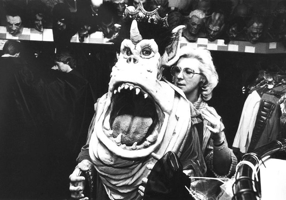 "**For Alternate Crop** Dean Johnson prepares for Halloween with a new ""Great Goblin"" face, with the assistance of Claudia Ostrom. The elaborate mask, one of several that will dot the streets Saturday night, is found at Hazel's Costumes, 1515 N. Portland. Photographed on Oct. 22, 1982. Archive Photo by Renee Lynn."
