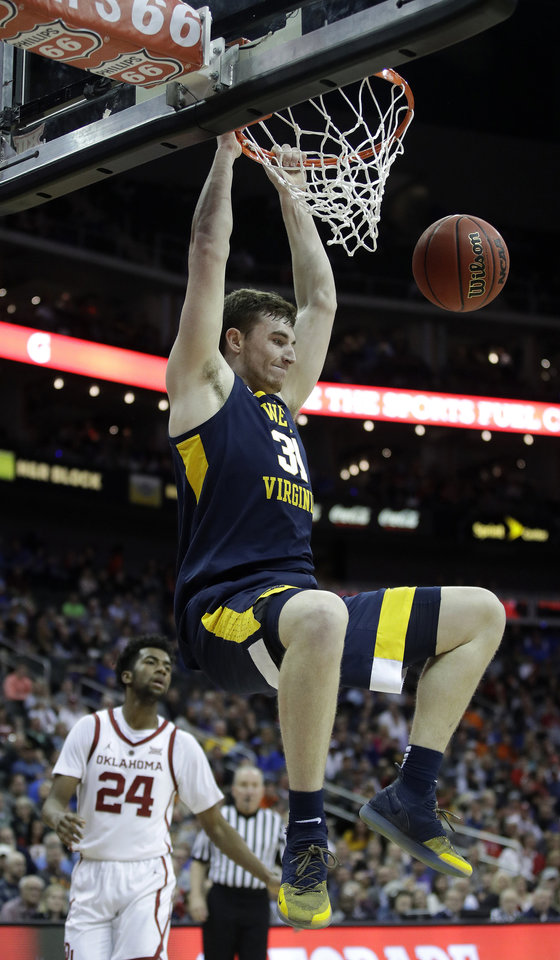 Photo - West Virginia's Logan Routt dunks during the first half of an NCAA college basketball game against Oklahoma in the Big 12 men's tournament Wednesday, March 13, 2019, in Kansas City, Mo. (AP Photo/Charlie Riedel)
