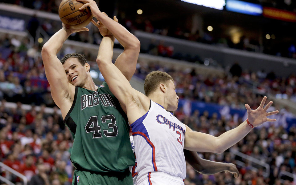 Photo - Boston Celtics forward Kris Humphries, left, pulls a rebound away from Los Angeles Clippers forward Blake Griffin during the second half of an NBA basketball game in Los Angeles, Wednesday, Jan. 8, 2014. (AP Photo/Chris Carlson)