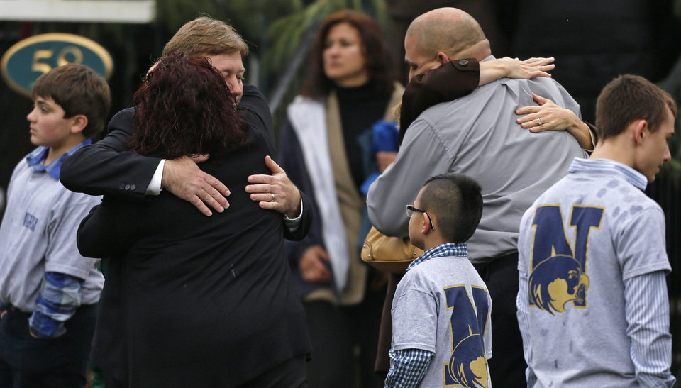 Photo - Families embrace while surrounded by children wearing Newtown school shirts outside the funeral for six-year-old shooting victim Jack Pinto in Newtown, Conn., Monday, Dec. 17, 2012. A gunman opened fire at Sandy Hook Elementary School in the town on Friday, killing 26 people, including 20 children before killing himself. (AP Photo/Charles Krupa)