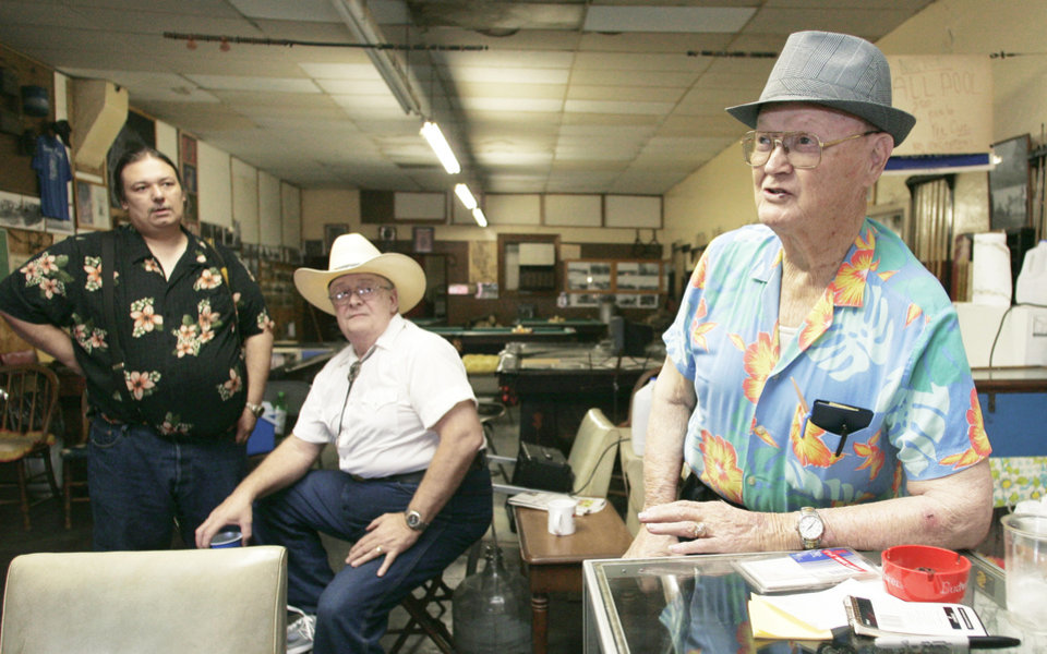 "Orval ""Hoppy"" Ray, right, runs a pool hall, makeshift museum, along Picher's main drag. In this photo from July 8, his grandson Steve Ray, left, and son Steven Ray look on. AP Photo"