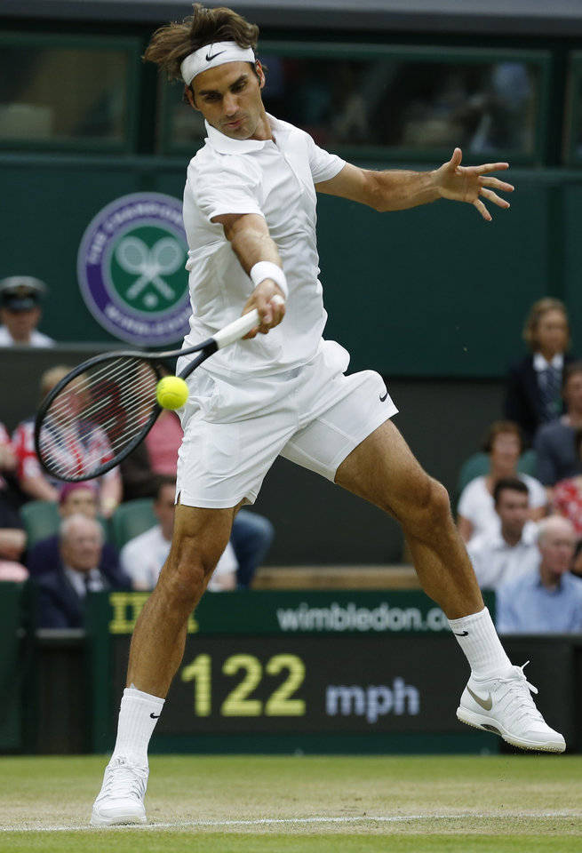 Photo - Roger Federer of Switzerland plays a return to Santiago Giraldo of Colombia during their men's singles match at the All England Lawn Tennis Championships in Wimbledon, London, Saturday, June 28, 2014. (AP Photo/Ben Curtis)