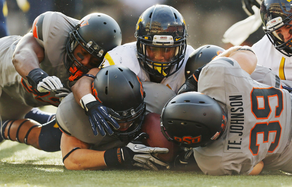 Photo - Oklahoma State's Nico Ornelas (41), middle, recovers a fumbled West Virginia kickoff return between teammates Kris Catlin (32), left, and Teddy Johnson (39), right, while underneath West Virginia's Andrew Buie (13) in the second quarter during a college football game between Oklahoma State University (OSU) and West Virginia University (WVU) at Boone Pickens Stadium in Stillwater, Okla., Saturday, Nov. 10, 2012. Photo by Nate Billings, The Oklahoman