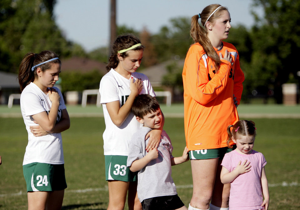 Photo - Rochelle Garcia, Nicole Voss  and Elyse Hight, Bishop McGuinness High School girls soccer team members, sing the National Anthem with Rob Medley, 6, and Ruthie Medley, 4, at a soccer game on Tuesday at Bishop MicGuinness. Rob Medley is a student at Good Shepherd Catholic School at Mercy.  SARAH PHIPPS - SARAH PHIPPS