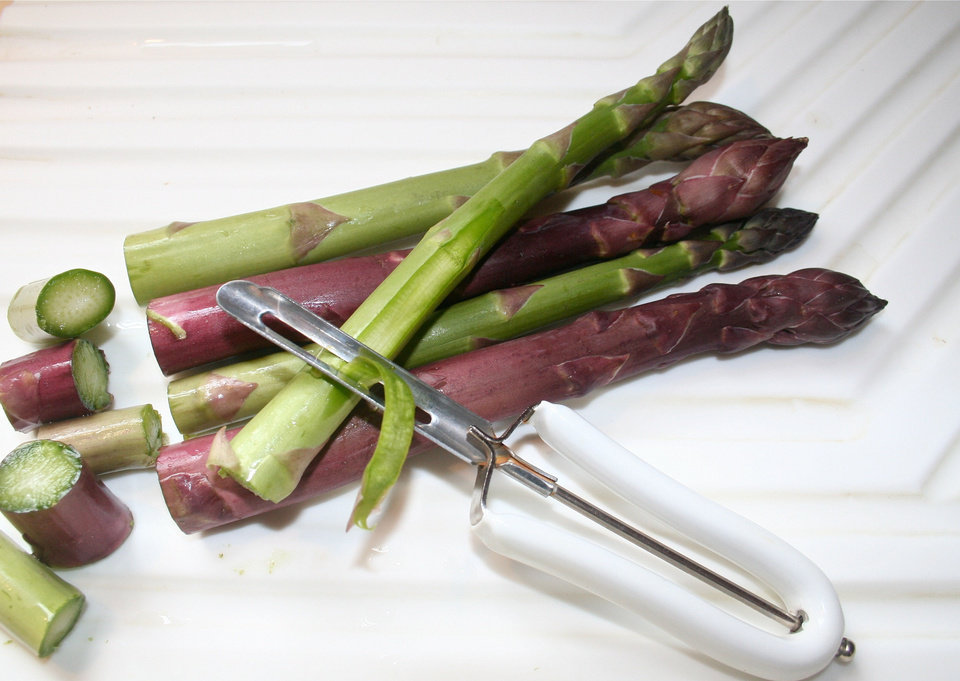 Photo - Spring rains may make it necessary to use a vegetable peeler to remove some of the lower leaflets along asparagus stems. These tend to pick up tiny bits of soil during heavy spring rains as the asparagus works its way up through the soil. Trim the bottoms of the asparagus to keep the spears at a uniform length then use the peeler to slice away the leaflets before cooking.      SHERREL JONES - THE OKLAHOMAN