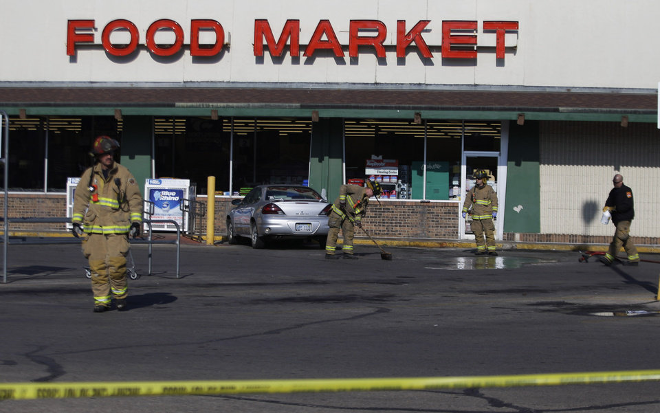 Photo - Firefighters clean up the scene outside a grocery store where two police officers were fatally shot as they investigated a suspicious vehicle, in Topeka, Kan., Monday, Dec. 17, 2012. A suspect in the killings is dead after a nearly two-hour armed standoff, authorities said Monday. (AP Photo/Orlin Wagner)
