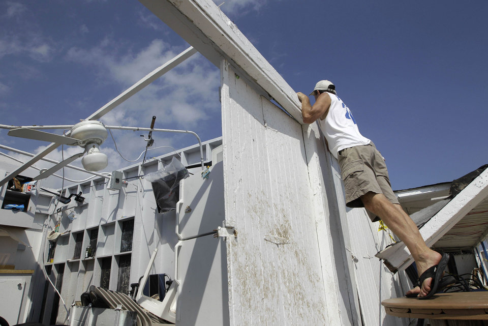 Photo -   Cabana owner Bill Ryan looks into other roofless cabanas at the Breezy Point Surf Club in the Queens borough of New York, Saturday, Sept. 8, 2012, after a severe weather storm passed through the area. A tornado swept out of the sea and hit the beachfront neighborhood in New York City, hurling debris in the air, knocking out power and startling residents who once thought of twisters as a Midwestern phenomenon. Firefighters were still assessing the damage, but no serious injuries were reported and the area affected by the storm appeared small. (AP Photo/Kathy Willens)