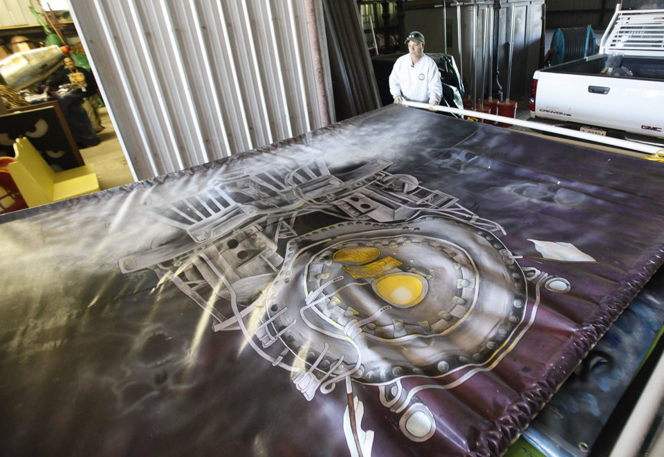 Photo - Graphic Designer Cliff Casey places a large painted display onto a trailer in preparation for the annual Haunt the Zoo at the Oklahoma City Zoo in Oklahoma City, OK, Friday, October 19, 2012,  By Paul Hellstern, The Oklahoman