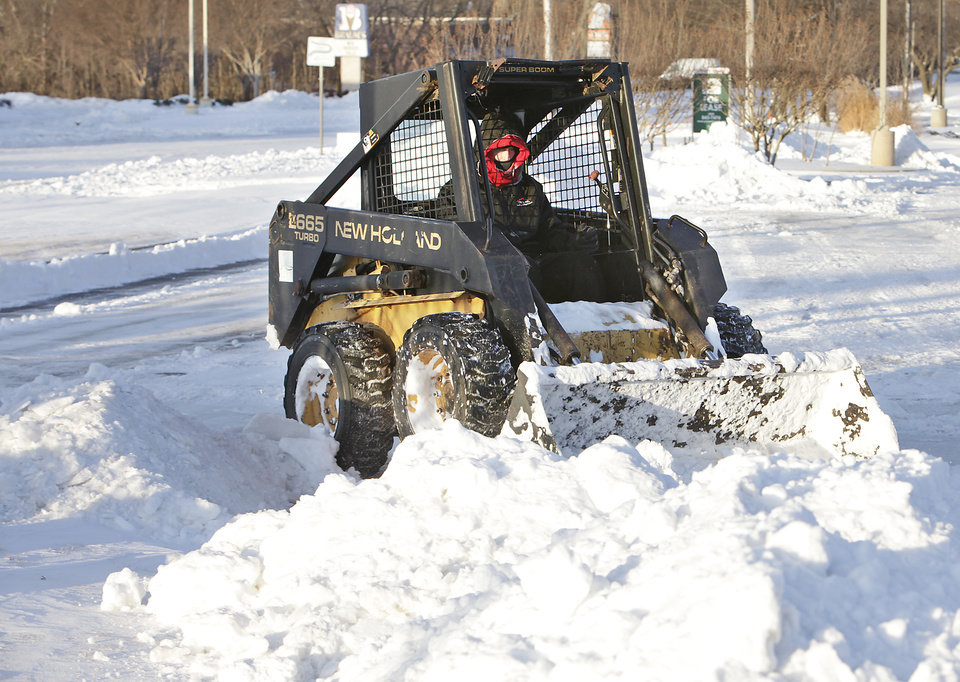 Photo - Rick Hinds clears a parking lot at Edmond Road and Santa Fe in Edmond, Wednesday, February 2, 2011. Hinds said he started his day at 7 a.m. after working all day yesterday. Photo by David McDaniel, The Oklahoman