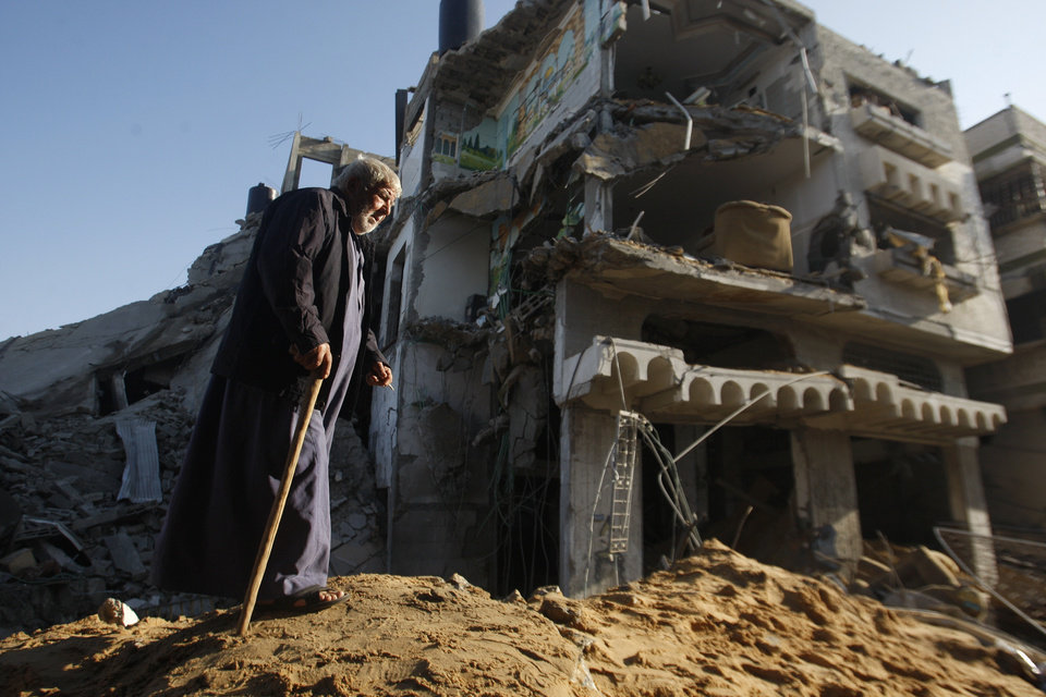 Photo -   An elderly Palestinian walks next to a destroyed building after an Israeli strike in Gaza City, Tuesday, Nov. 20, 2012. Efforts to end a week-old convulsion of Israeli-Palestinian violence drew in the world's top diplomats on Tuesday, with President Barack Obama dispatching his secretary of state to the region on an emergency mission and the U.N. chief appealing from Cairo for an immediate cease-fire. (AP Photo/Hatem Moussa)