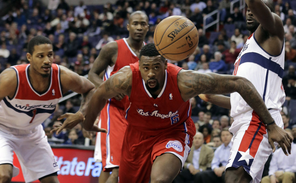 Photo - Los Angeles Clippers center DeAndre Jordan (6) goes after the loose ball with Washington Wizards forward Trevor Ariza (1) and center Emeka Okafor (50) in the first half of an NBA basketball game Monday, Feb. 4, 2013 in Washington. (AP Photo/Alex Brandon)