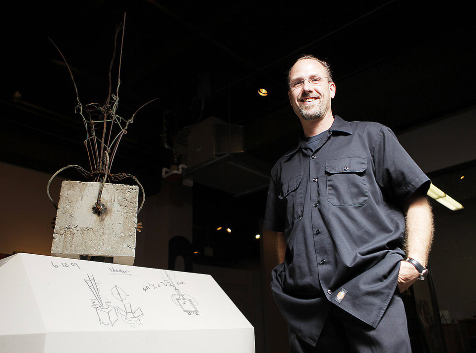 Photo - Eric Wright poses for a photo next to his art,