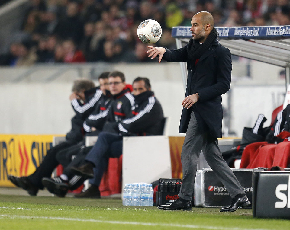 Photo - Bayern head coach Pep Guardiola of Spain carries a ball during a German first soccer division Bundesliga match between VfB Stuttgart and FC Bayern Munich in Stuttgart, Germany, Wednesday, Jan. 29, 2014. (AP Photo/Michael Probst)